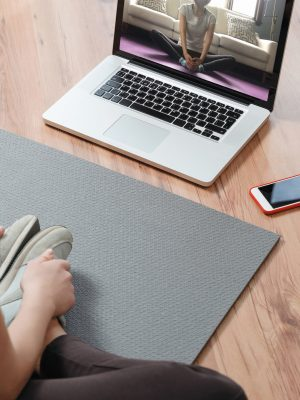 Yoga teacher conducting virtual class at home on a video conference. Young beautiful woman doing an online yoga class in her living room with laptop. Home fitness and workout concept